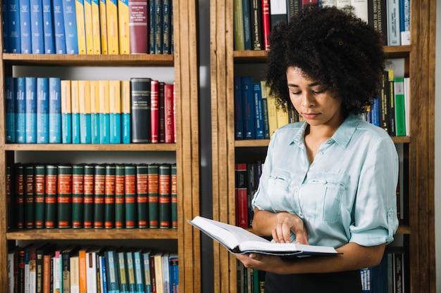 Libro de lectura de mujer negra en biblioteca