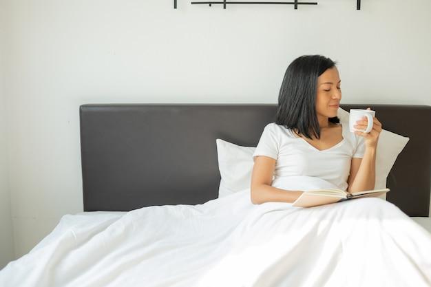 Libro de lectura de mujer con taza de café en casa en el dormitorio.
