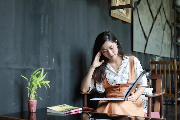 Libro de lectura de las mujeres asiáticas y sonriente y feliz relajación en una cafetería