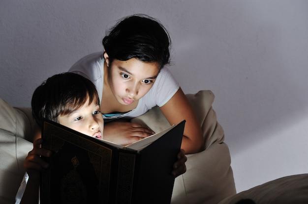 Libro de lectura de niño sorprendido, luz en la oscuridad
