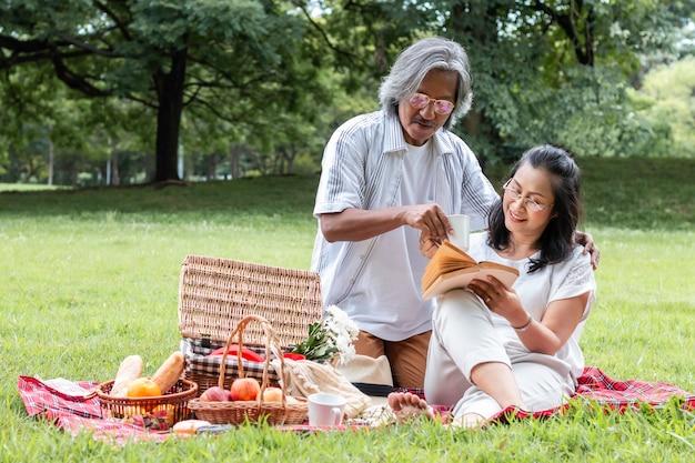 Libro de lectura de pareja senior asiático y picnic en el parque.