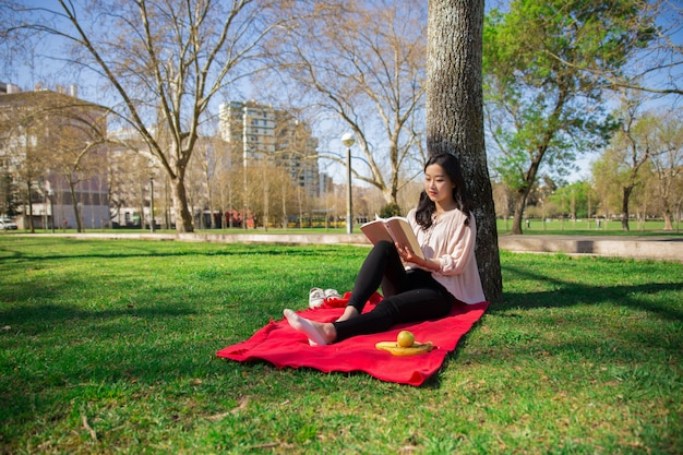 Libro de lectura pensativo serio de la muchacha del estudiante