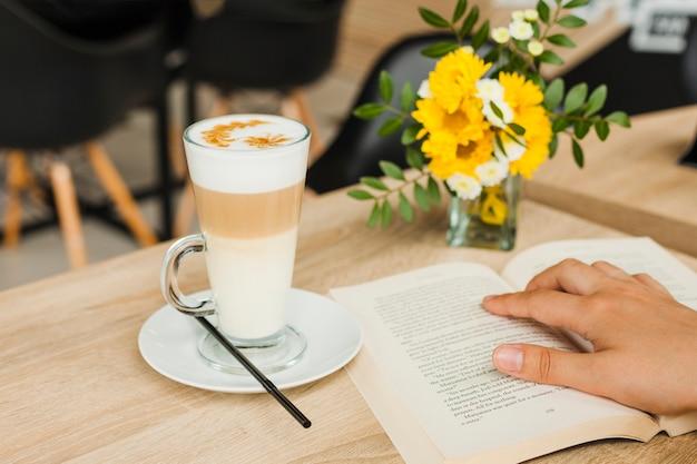 Libro de lectura de la persona cerca de la taza de café en el escritorio en la cafetería