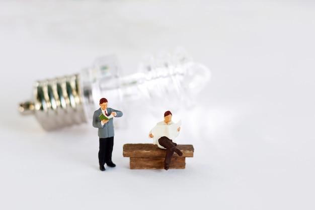 Libro de lectura de personas en miniatura con idea de lámpara, educación o concepto de negocio.
