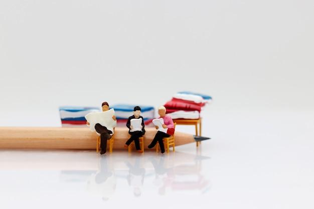 Libro de lectura de personas en miniatura con lápiz, concepto de educación.