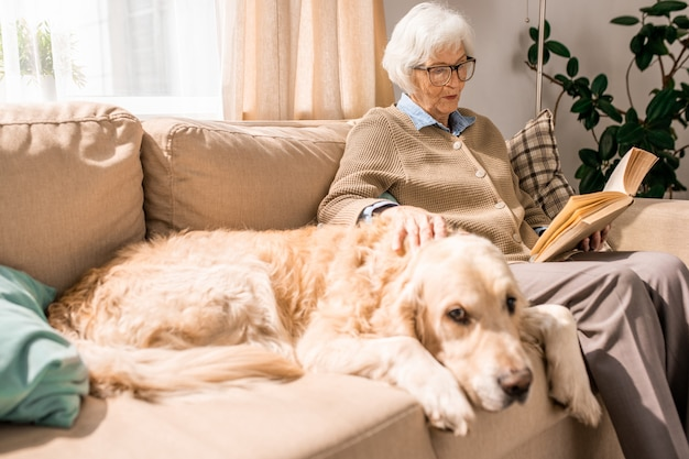 Libro de lectura de señora mayor con perro