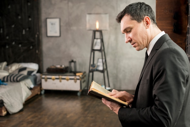 Libro de lectura serio joven del hombre de negocios