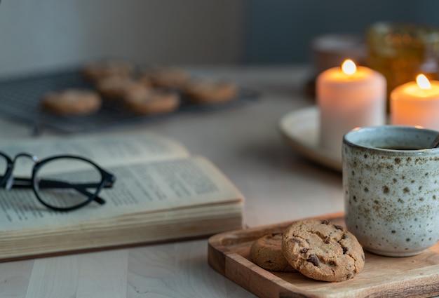 Libro de lectura sobre la acogedora noche de invierno con velas, té y galletas.