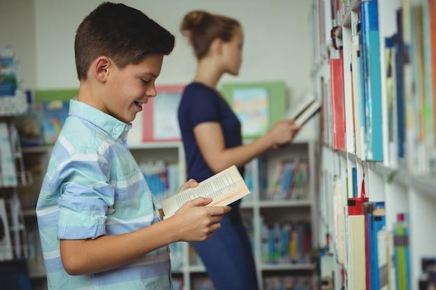 Libro de lectura sonriente del colegial en biblioteca
