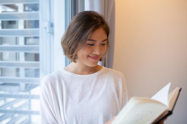 Libro de lectura sonriente de la mujer joven en la ventana en casa