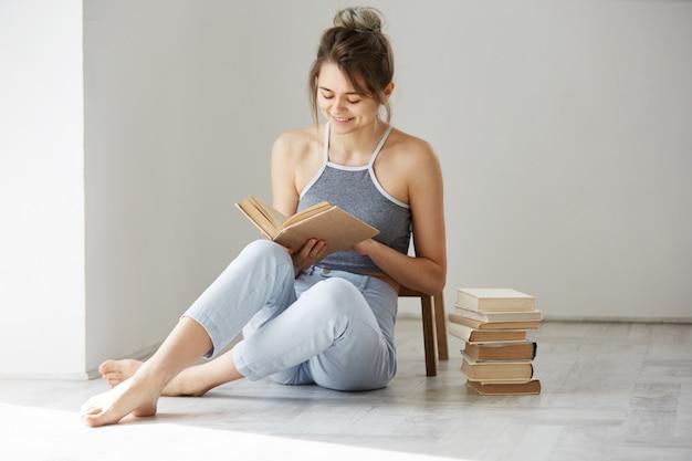 Libro de lectura sonriente de la mujer tierna hermosa joven que se sienta en piso sobre la pared blanca temprano por la mañana.
