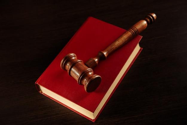 Libro de leyes con un mazo de jueces descansando en la parte superior de las páginas en una sala de audiencias u oficina de la ley