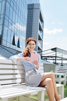 Libro en línea. hermosa trabajadora remota de moda que se siente interesada mientras lee un libro en línea durante su descanso