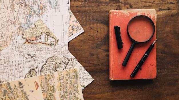 Libro y lupa cerca de los mapas