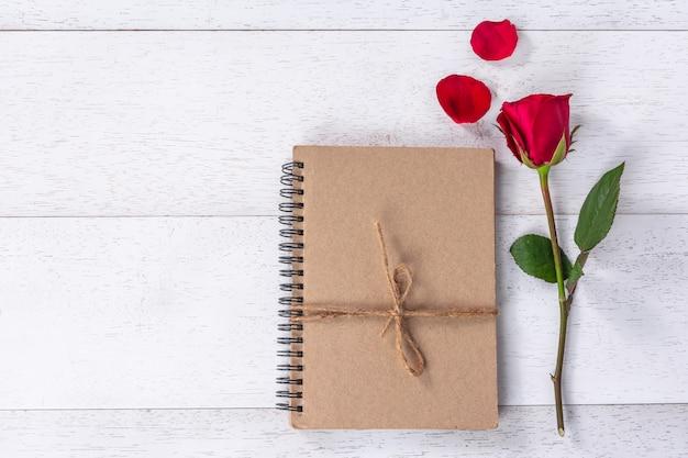 Libro de manualidades atado con una cuerda de cáñamo decorada con rosas rojas y pétalos en una mesa de madera blanca