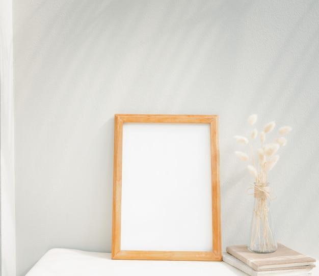 Libro de manualidades de marco de imagen de maqueta en blanco y flor seca en florero de vidrio sobre mesa beige y pared de cemento