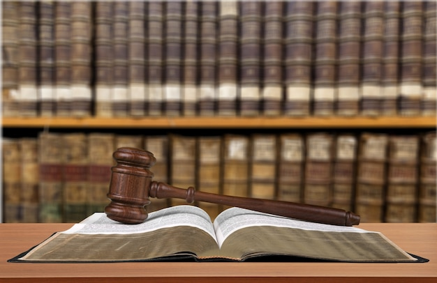 Libro con martillo de juez sobre fondo de estanterías
