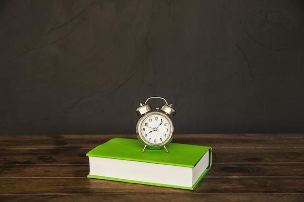 Libro en la mesa con despertadores