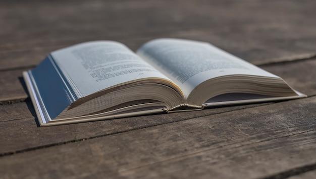 Libro moderno abierto en el escritorio de madera vieja con el concepto de conocimiento a la luz del día