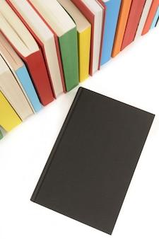 Libro negro liso con fila de libros coloridos
