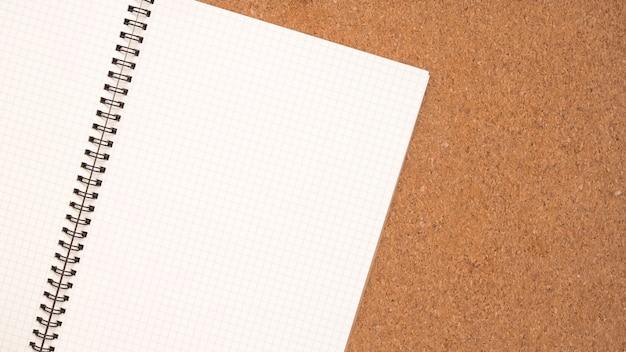 Libro de notas, página de papel blanco y tablero de madera.