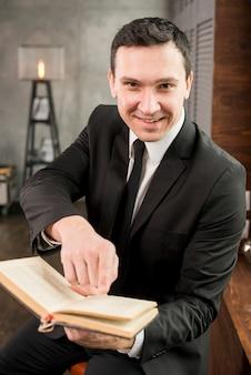 Libro de ofrecimiento del hombre de negocios contento joven sonriente