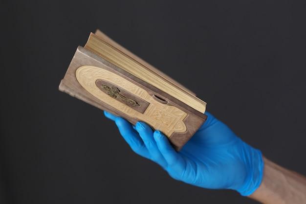 Libro de oraciones en manos de los hombres con guantes médicos azules.