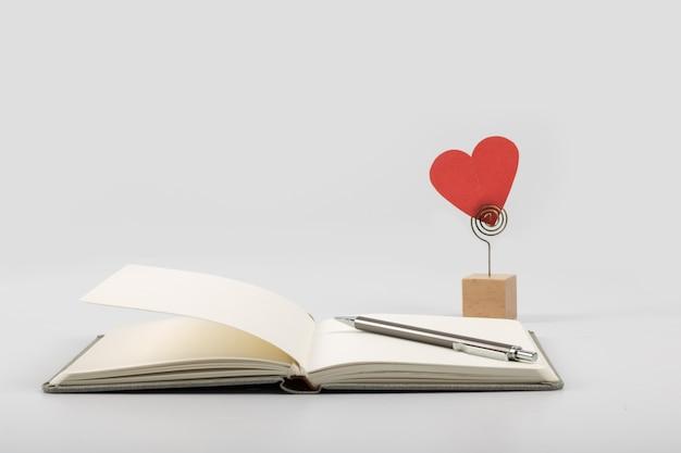 Libro y papel cortado amor y fondo blanco.