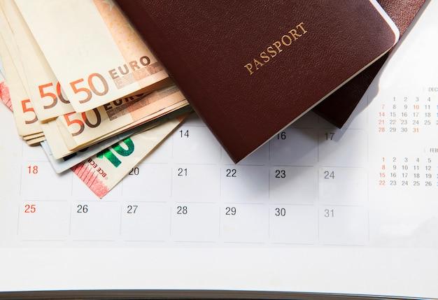 Libro de pasaportes de tapa roja y billete de 50 euros en fecha del calendario