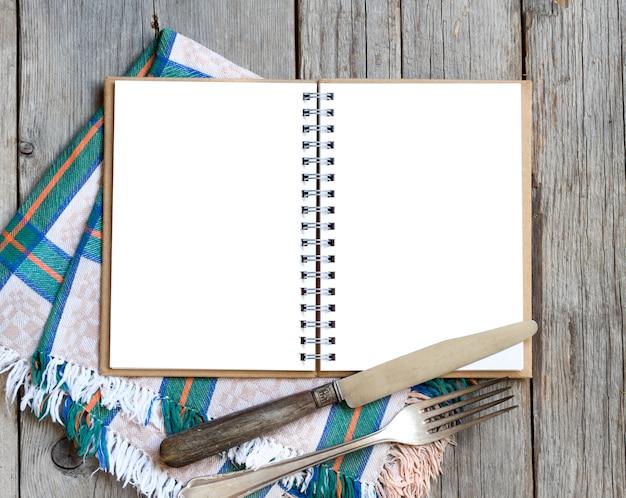Libro de recetas de cocina en blanco sobre servilleta en mesa de madera con vista superior de tenedor y cuchillo
