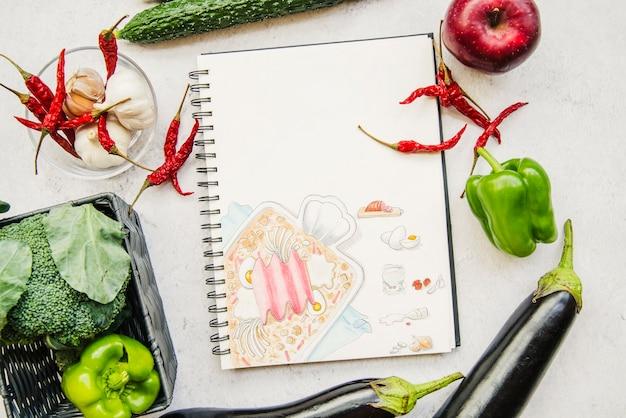 Libro de recetas e ingredientes sobre fondo blanco