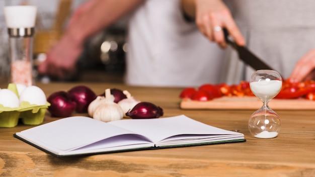 Libro de recetas y reloj de arena en la cocina.