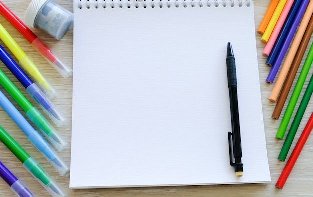 Libro de recuerdos, rotuladores y lápices de colores sobre la mesa.
