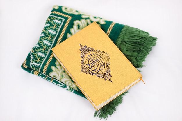 El libro sagrado al corán y alfombra de oración aislado sobre fondo blanco.