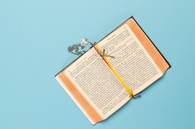 Libro sagrado y collar con cruz
