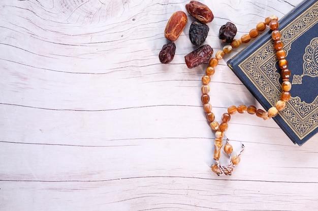 Libro sagrado corán y fecha fruta en mesa de madera