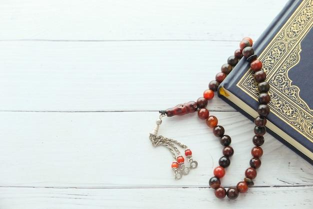 Libro sagrado corán y rosario musulmán en mesa con espacio de copia.
