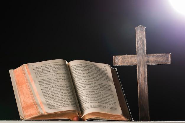 Libro sagrado y cruz en luz de luna