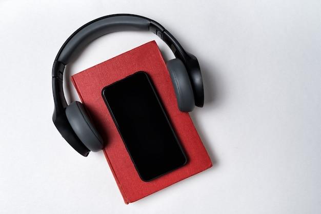 Libro sobre fondo blanco con auriculares puestos en ellos. concepto de libro electrónico o audiolibro. vista superior copia espacio