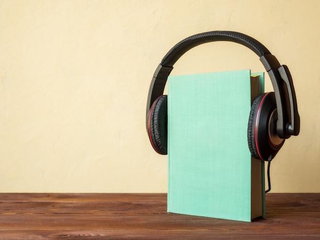 Libro sobre la mesa con auriculares