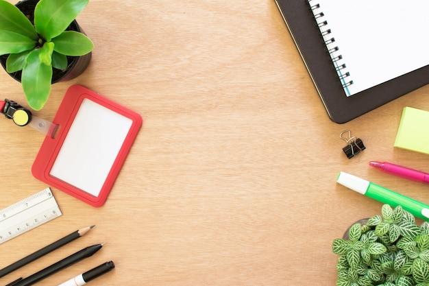 Libro, sujetapapeles, lápiz, regla, bolígrafo resaltar, tarjeta de empleado, post-it y pote de árbol en escritorio de madera marrón rústico
