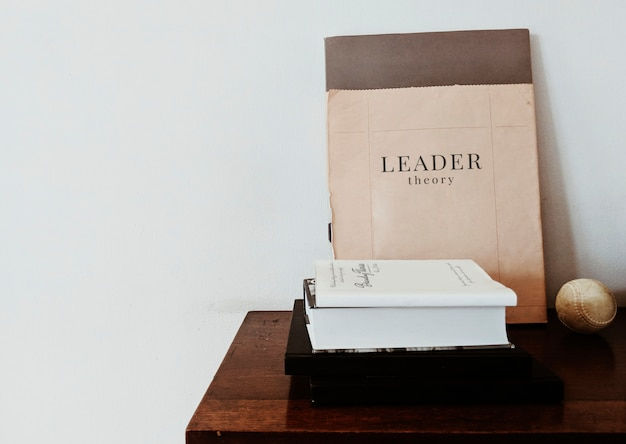Libro de teoría del líder con una pelota de béisbol sobre la mesa.