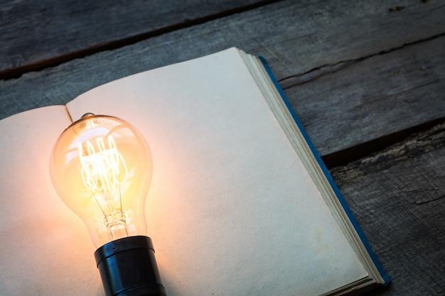 Libro de la vendimia y la bombilla de luz en la mesa de madera