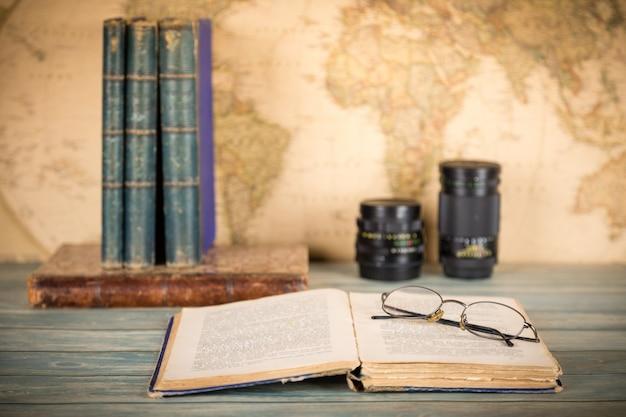 Libro viejo abierto con gafas en el fondo retro del mapa