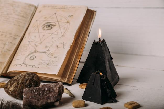 Libro viejo abierto con hechizos mágicos, runas, vela negra