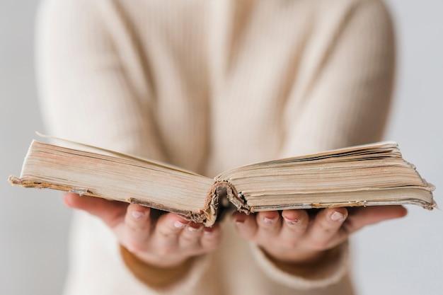 Un libro viejo abierto en la mano de la mujer.