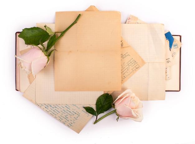 Libro viejo abierto y rosas con copia espacio aislado sobre superficie blanca