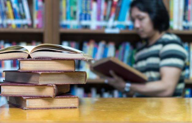 Libro viejo en el escritorio en la biblioteca con el hombre leyendo el fondo del libro