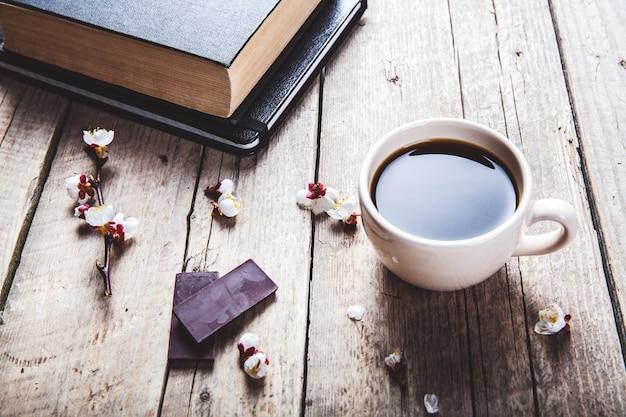 Libro vintage abierto con rama de flor de cerezo en mesa de madera. una taza de café