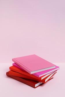 Libros de alto ángulo con fondo rosa